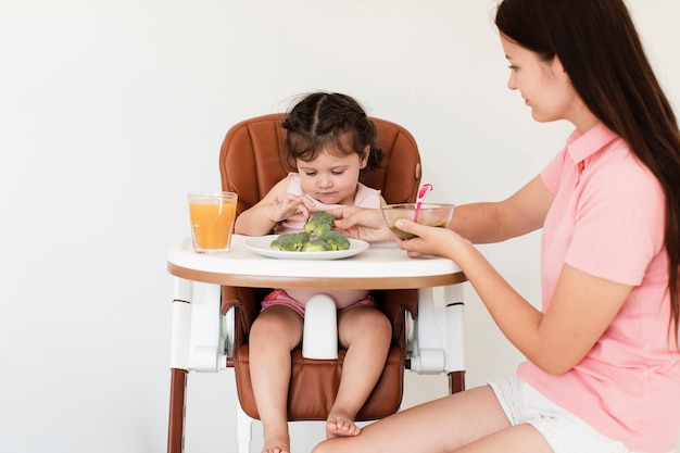 Mother giving broccoli to her daughter Free Photo
