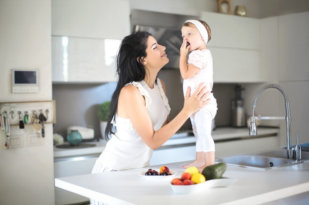 Mother giving food to her baby in the kitchen Premium Photo