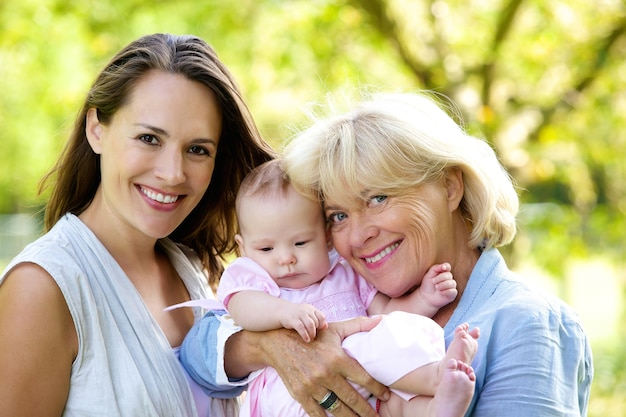 Mother and grandmother smiling with baby outdoors Premium Photo