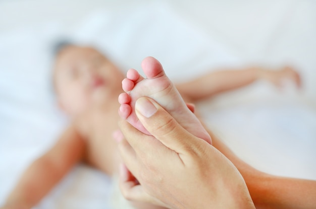 Mother hand massaging feet of infant baby on the bed at home. Premium Photo