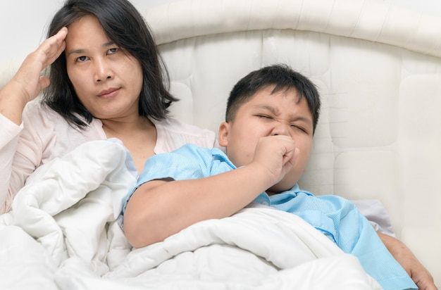 Mother has a headache because her son is sick and coughs. Premium Photo