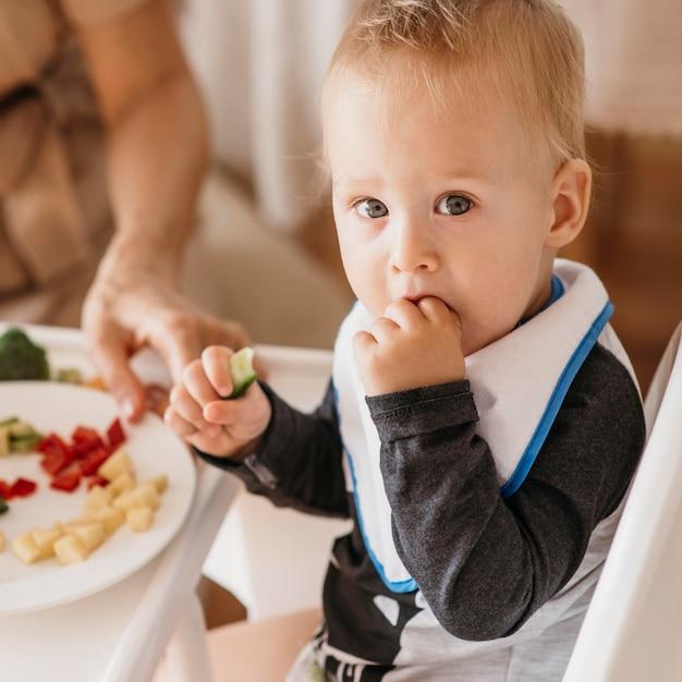 Мать помогает милому ребенку выбрать, какую еду съесть Premium Фотографии