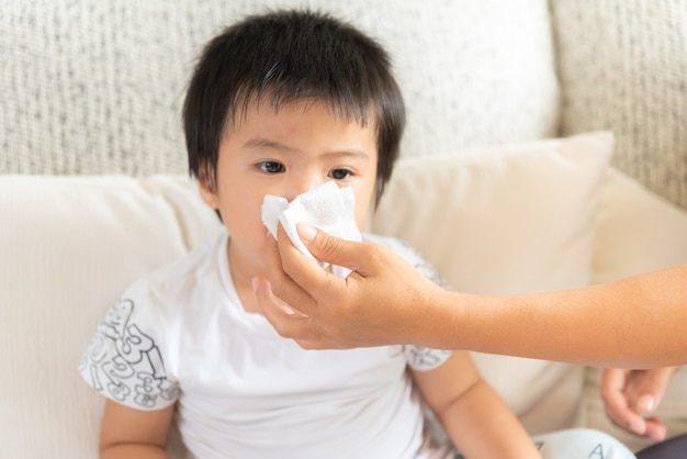 Mother helping daughter blow her nose at home in the living room Premium Photo