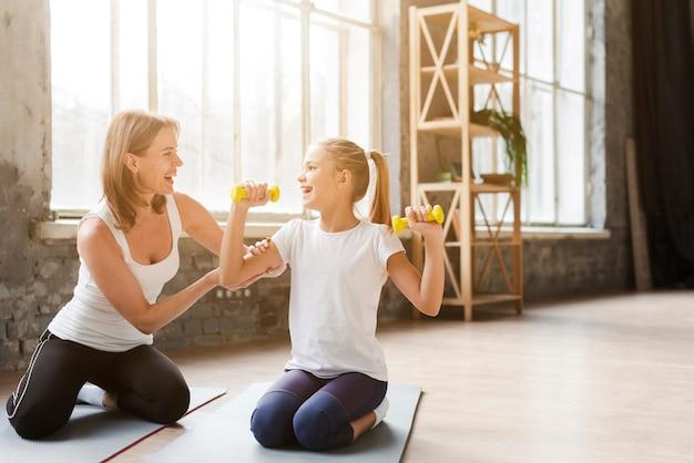 Мать помогает дочери, держа вес на коврик для йоги Бесплатные Фотографии