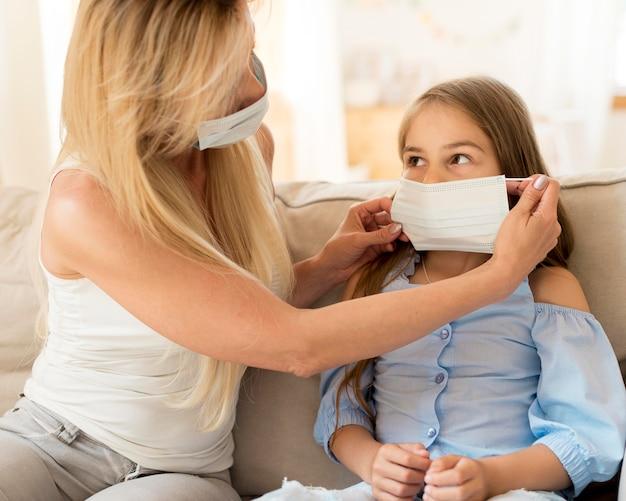 Мать помогает дочери надеть медицинскую маску Бесплатные Фотографии