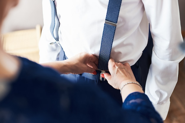Mother helping groom getting ready in the morning for wedding ceremony. Premium Photo