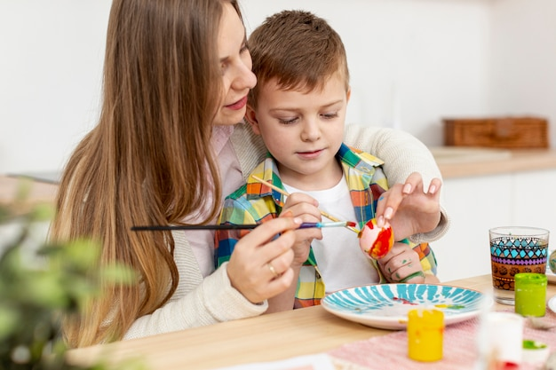 Mother helping son to paint eggs Free Photo