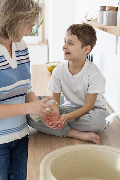 母親は子供が手を洗うのを手伝います 無料写真