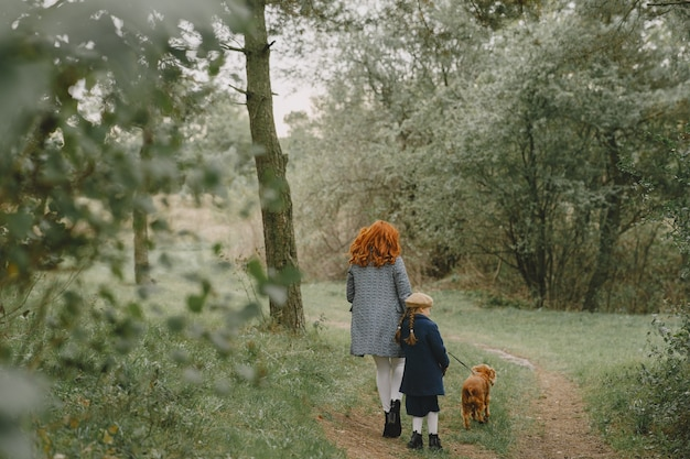 Mother and her daughter playing with dog. family in autumn park. pet, domestic animal and lifestyle concept. autumn time. Free Photo