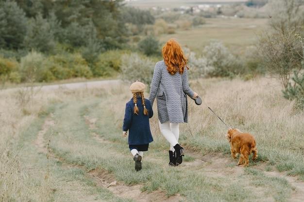 Madre e figlia che giocano con il cane. famiglia nella sosta di autunno. pet, animali domestici e concetto di stile di vita. tempo d'autunno. Foto Gratuite