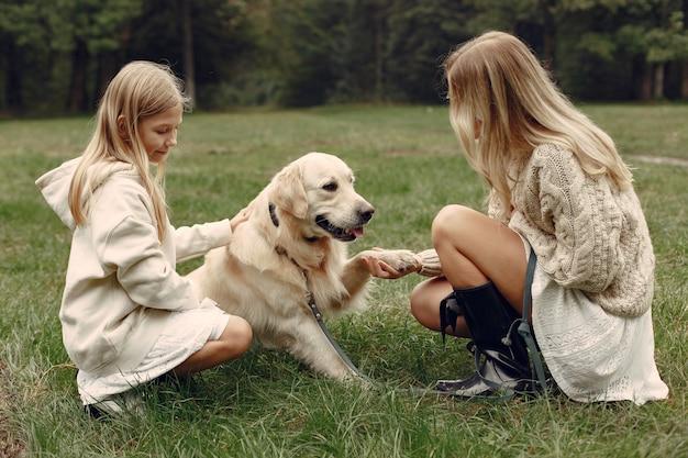 Madre e figlia che giocano con il cane. famiglia nella sosta di autunno. pet, animali domestici e concetto di stile di vita Foto Gratuite