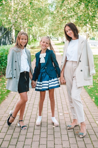 Mother and her daughters to school. adorable little girls feeling very excited about going back to school Premium Photo