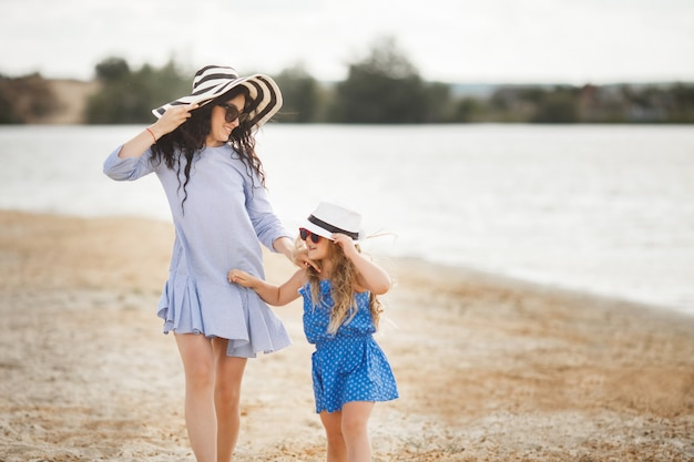 Mother and her little daughter having fun at the coast. young pretty mom and her child playing near the water Premium Photo
