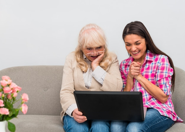 Mother and her young daughter sitting together on sofa looking at laptop Free Photo