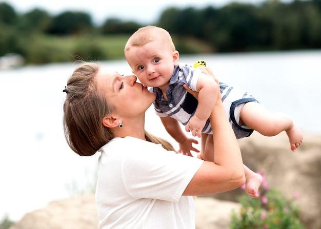 Мать держит и целует сына Premium Фотографии