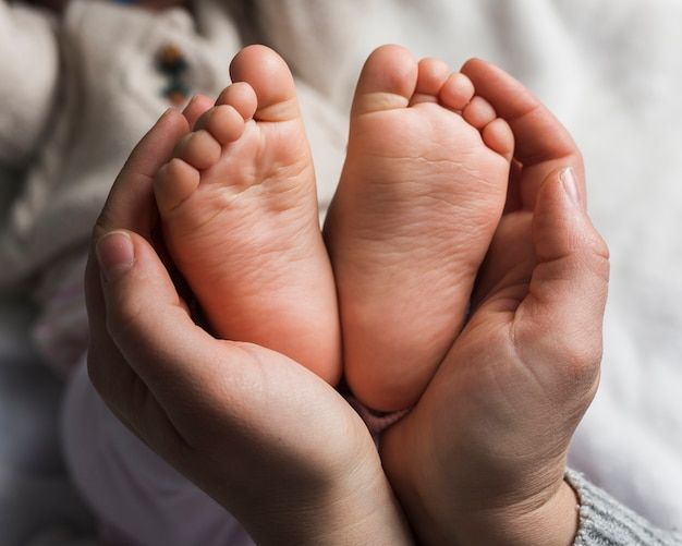 Mother holding baby feet close up Free Photo