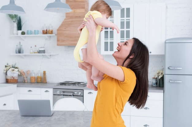 Mother holding baby in the kitchen Free Photo