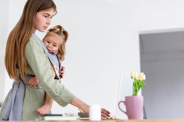 Мать держит девушку во время работы Бесплатные Фотографии