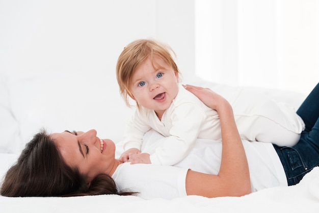 Mother holding smiling baby Free Photo