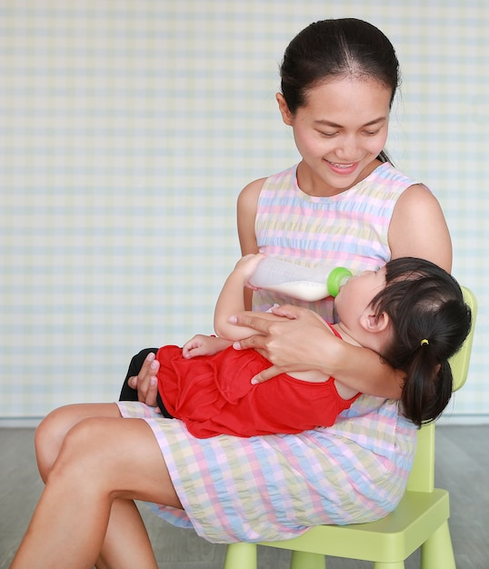 Mother hug her cute asian child girl drinking from a bottle at the living room Premium Photo