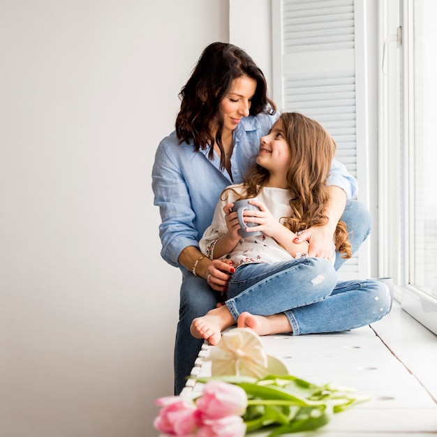 Mother hugging daughter from behind on window sill Free Photo