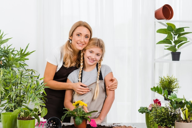 Mother hugging daughter in greenhouse Free Photo