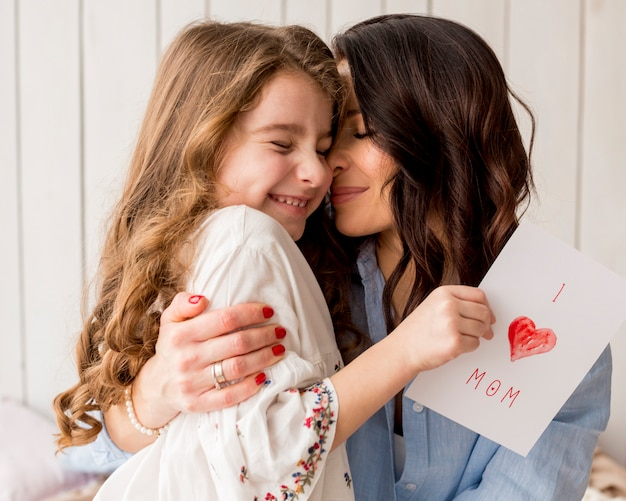 Mother hugging daughter with greeting card Free Photo