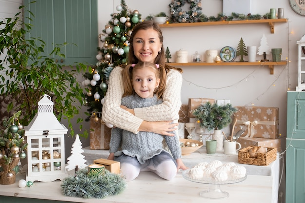 Mother hugging her little girl in christmas kitchen at home. Premium Photo