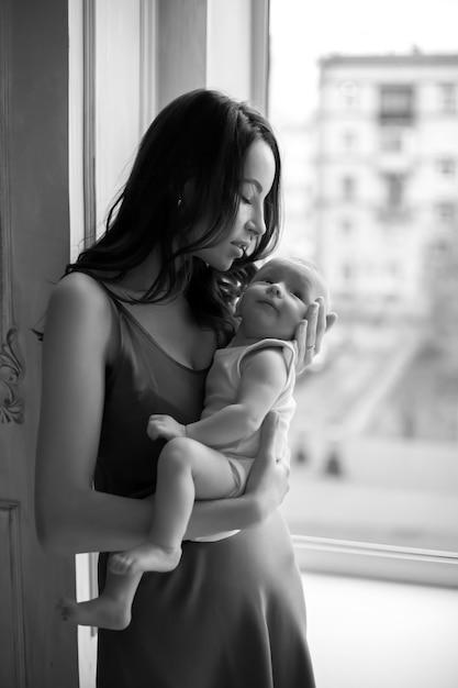 ネグリジェの母親は、窓際に生まれたばかりの男の子を腕に抱きます Premium写真