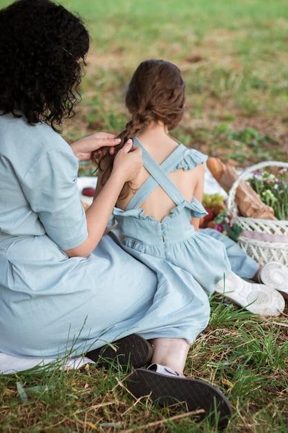 파란 드레스에 어머니는 그녀의 딸 머리를 띠 프리미엄 사진