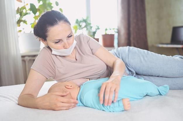 Мать в защитной маске с новорожденным младенцем в комбинезоне кормит грудью грудным молоком Premium Фотографии