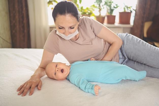 Мать в защитной маске с новорожденным младенцем в синем комбинезоне обнимает его, лежа на кровати Premium Фотографии