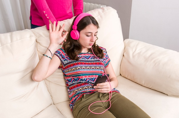 Mother is angry. teen girl with pink headphones is listening music with her phone at home. Premium Photo