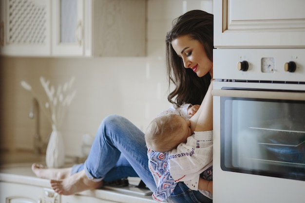 Mother is breastfeeding in the kitchen Free Photo