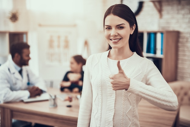 Mother is posing giving thumbs up in clinic. Premium Photo