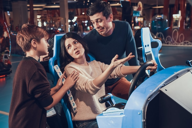 Mother is riding car in arcade. family is comforting her. Premium Photo
