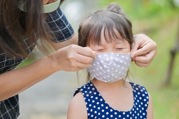 Мама носит маску из ткани для защиты маленькой девочки от коронавируса, когда ребенок покидает дом Premium Фотографии
