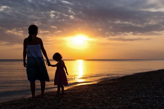 Mother and kid on sunset beach Premium Photo