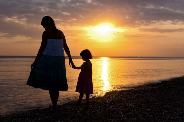 Mother and kid on sunset beach Premium Photo
