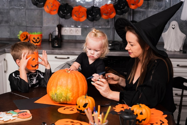 Mother and kids carving a pumpkin Free Photo