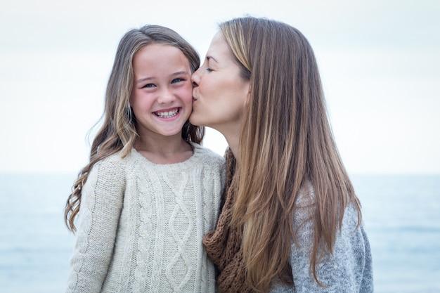 Mother kissing daughter at beach Premium Photo