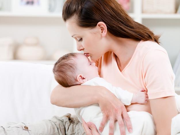 Мать целует спящего ребенка Бесплатные Фотографии