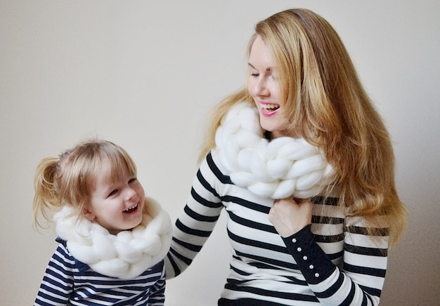 Mother and the little daughter in hats and scarf on a white background, family look Premium Photo