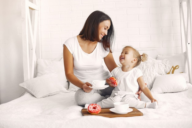 Mother and little daughter have a breakfast at home Free Photo