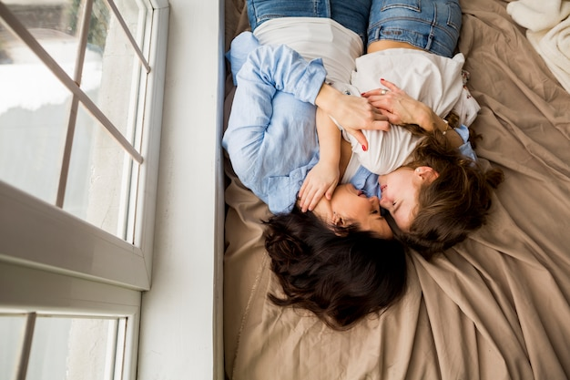 Mother and little daughter hugging on bed Free Photo