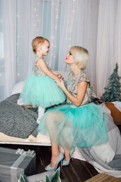 Mother and little daughter posing in the new year interior Premium Photo
