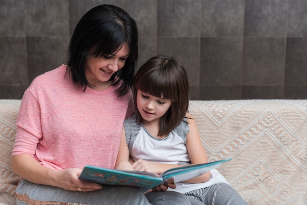 Mother and little daughter reading book on couch Free Photo