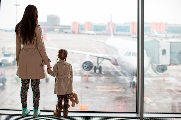 Mother and little girl in airport waiting for boarding Premium Photo