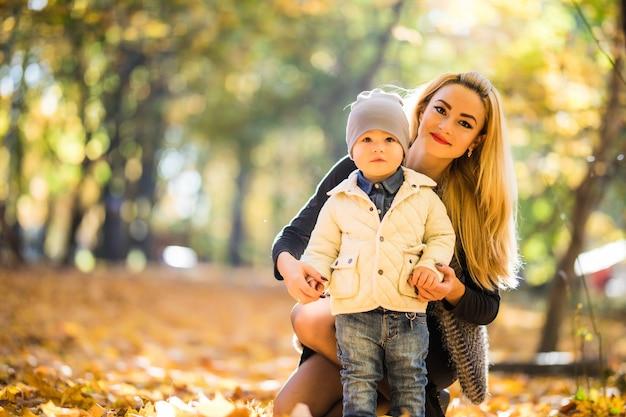 Madre e figlio piccolo nel parco o nella foresta, all'aperto. abbracciare e divertirsi insieme nel parco d'autunno Foto Gratuite