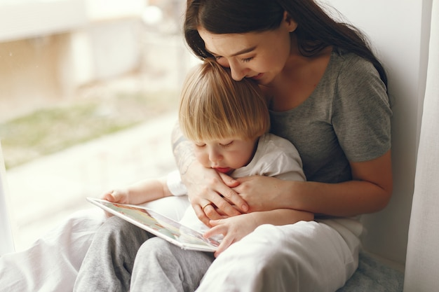 Mother and little son sitting on a windowsill Free Photo